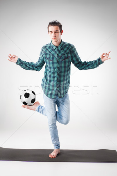Portrait  of young man, practicing yoga with football ball Stock photo © master1305