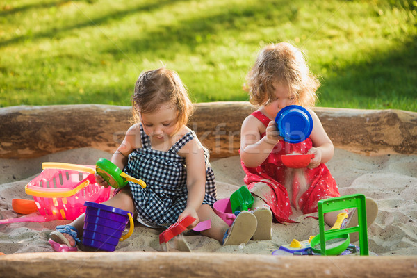 Stock photo: The two little baby girls playing toys in sand
