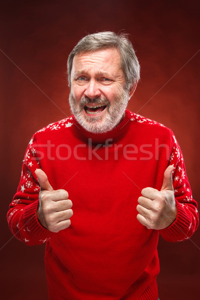 Elderly man showing ok sigh on a red background Stock photo © master1305
