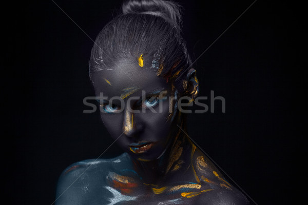 Portrait of a young woman who is posing covered with  black paint  Stock photo © master1305