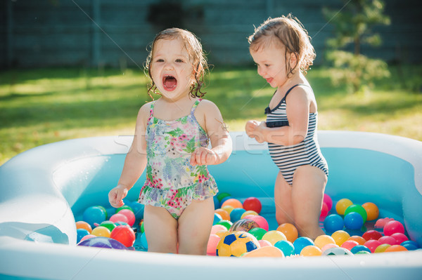The two little baby girls playing with toys in inflatable pool in the summer sunny day Stock photo © master1305