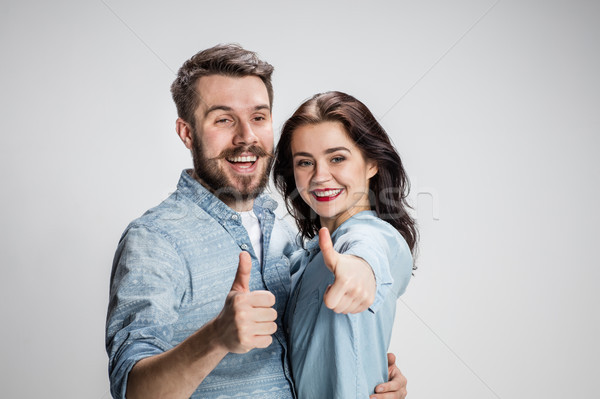 Two young smiling people with thumbs-up gesture Stock photo © master1305