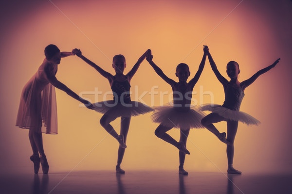 Three little ballerinas dancing with personal ballet teacher in dance studio Stock photo © master1305