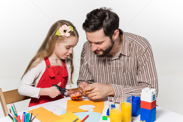 The daughter and father carving out paper applications  Stock photo © master1305