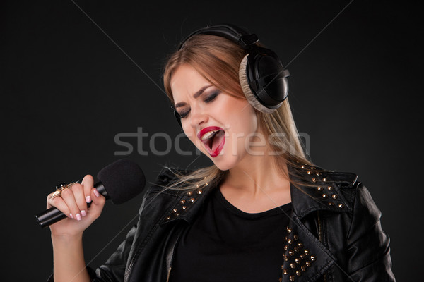 Portrait of a beautiful woman singing into microphone with headphones in studio on black background Stock photo © master1305