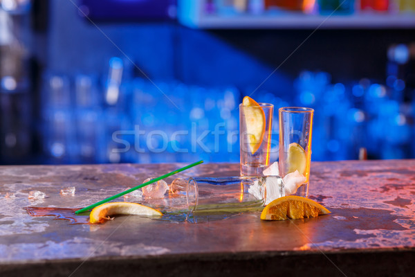 The spilled cocktails with ice cubes on blue color in the bar Stock photo © master1305