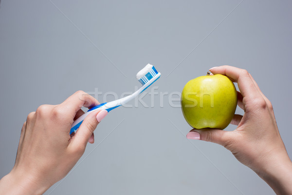 Toothbrush and apple in woman's hands on gray Stock photo © master1305