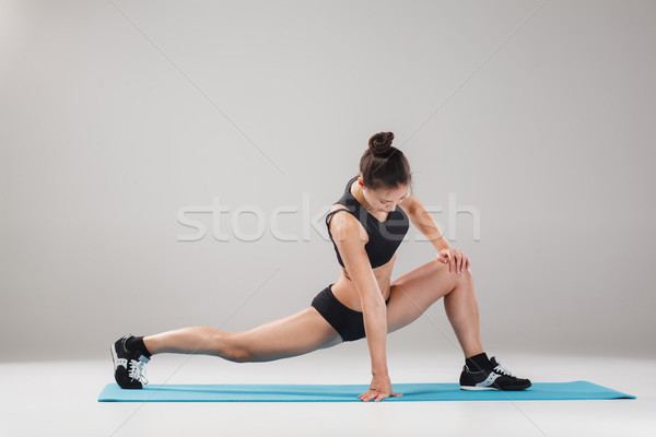 Beautiful sporty girl standing in acrobat pose or yoga asana Stock photo © master1305