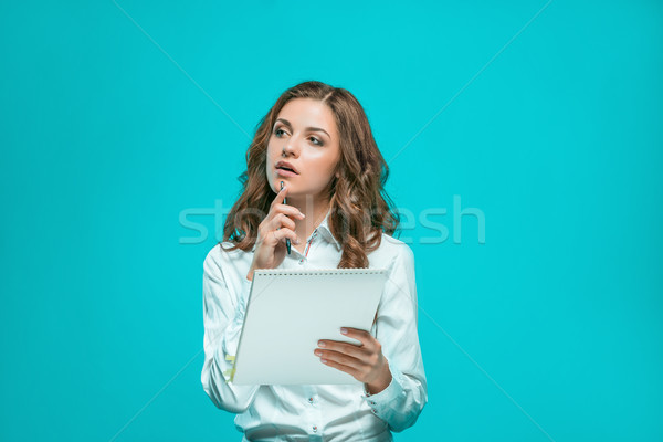 The thoughtful young business woman with pen and tablet for notes on blue background Stock photo © master1305
