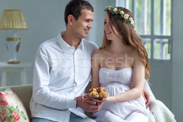 Cheerful young couple with baby shoes sitting at home Stock photo © master1305