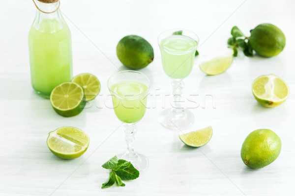Stock photo: Home lime liquor in a glass and fresh lemons, limes on the white wooden background