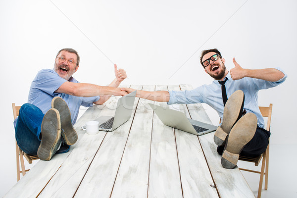 The two smiling businessmen with legs over table Stock photo © master1305