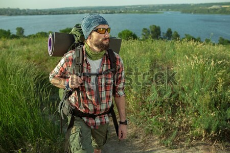 Young smilimg caucasian tourist hitchhiking along a road. Stock photo © master1305