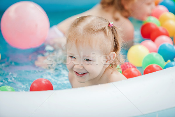 The little baby girl playing with toys in inflatable pool in the summer sunny day Stock photo © master1305
