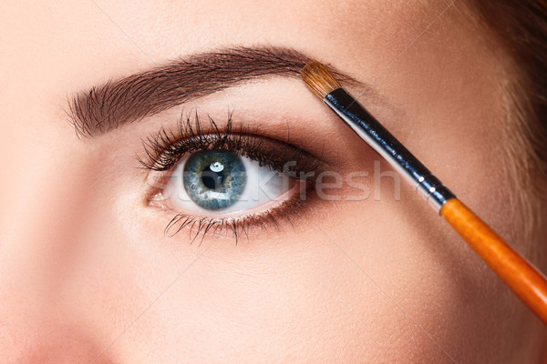 Beautiful female eyes with bright blue make-up and brush Stock photo © master1305