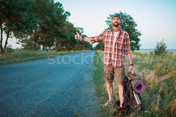 Young  caucasian tourist hitchhiking along a road. Stock photo © master1305