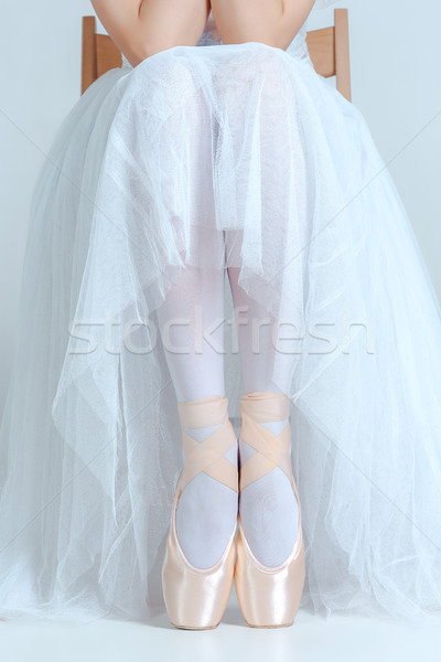 Professional ballerina sitting with her ballet shoes on the gray background Stock photo © master1305