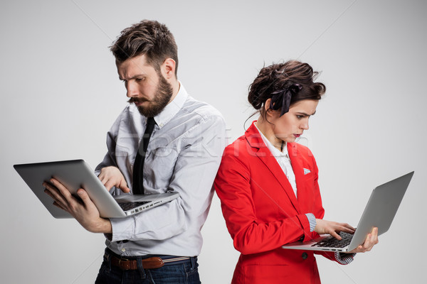 The young businessman and businesswoman with laptops  communicating on gray background Stock photo © master1305