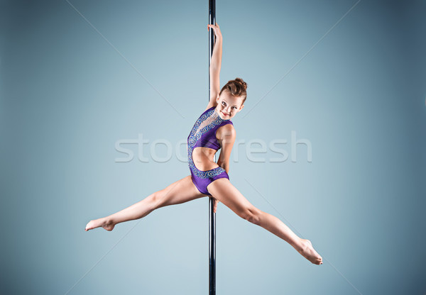 Stock photo: The strong and graceful young girl performing acrobatic exercises on pylon