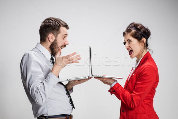 The young businessman and businesswoman with laptops on gray background Stock photo © master1305
