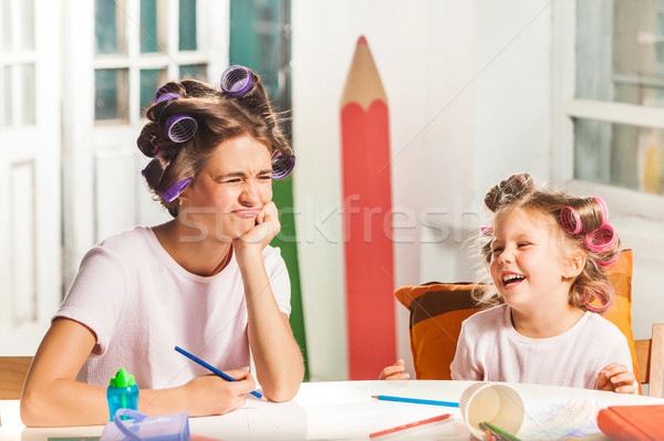 The young mother and her little daughter drawing with pencils at home Stock photo © master1305