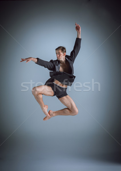 The young attractive modern ballet dancer jumping on gray background Stock photo © master1305