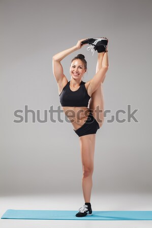 Muscular young woman athlete standing in the split on black  Stock photo © master1305
