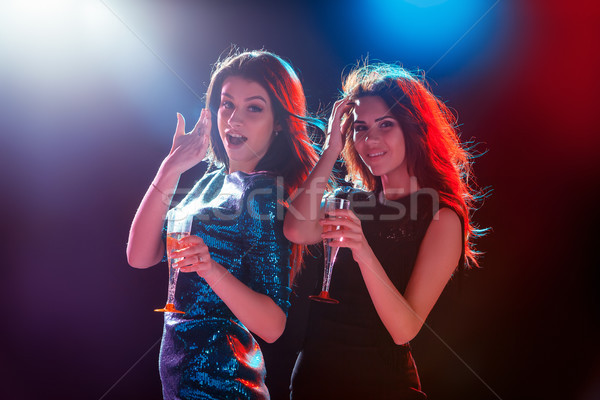 Stock photo: Two beautiful girls dancing at the party drinking champagne