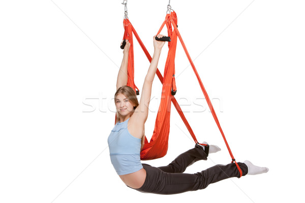 Young woman doing anti-gravity aerial yoga in  red hammock on a seamless white background. Stock photo © master1305