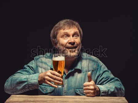 The smiling man in denim shirt with glass of beer Stock photo © master1305