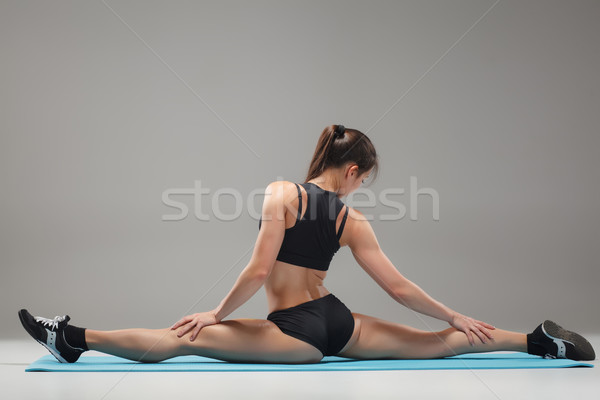 Muscular young woman athlete sitting in the split on gray  Stock photo © master1305