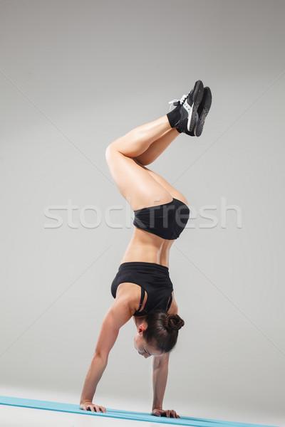 Gyönyörű sportos lány áll akrobata póz Stock fotó © master1305