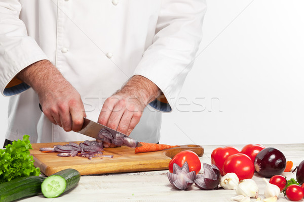 Chef cutting a onion on his kitchen Stock photo © master1305