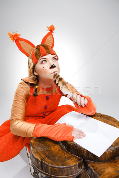 Young woman in image of squirrel writing with quill pen Stock photo © master1305