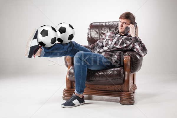 The portrait of fan with balls, holding phone on gray background Stock photo © master1305