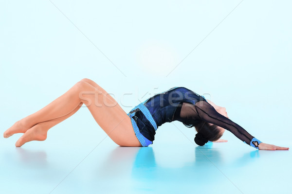 The girl doing gymnastics dance on a blue background Stock photo © master1305