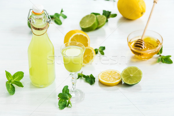 Home lime liquor in a glass and fresh lemons, limes on the white wooden background Stock photo © master1305
