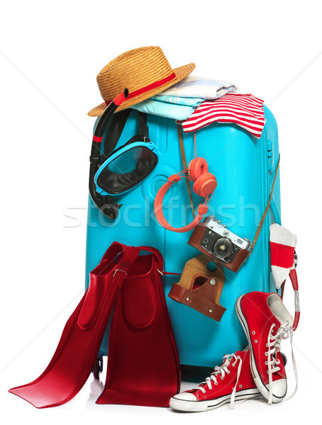 The blue suitcase, sneakers, clothing, hat, and retro camera on white background. Stock photo © master1305