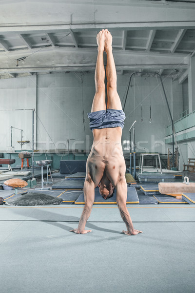 caucasian man gymnastic acrobatics equilibrium posture at gym background Stock photo © master1305