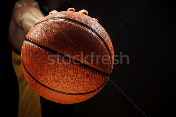 Silhouette view of a basketball player holding basket ball on black background Stock photo © master1305