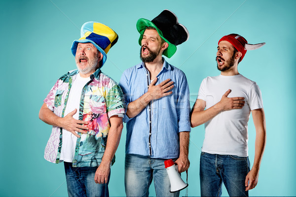 Stock photo: The three football fans singing the national anthem over blue
