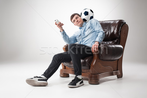 The portrait of fan with ball, holding  tv remote on white background Stock photo © master1305