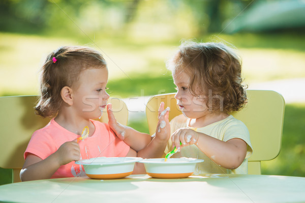 Two little girls sitting at a table and eating together against green lawn Stock photo © master1305
