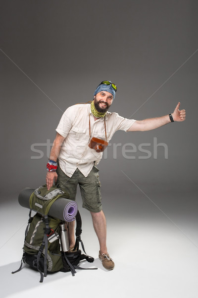 Male tourist with backpack hitchhiking on gray background Stock photo © master1305