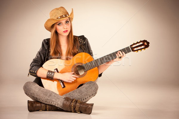 The beautiful girl in a cowboy's hat and acoustic guitar. Stock photo © master1305