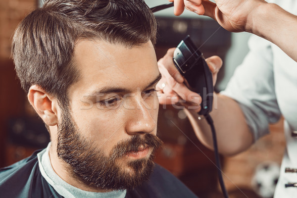 The hands of young barber making haircut  attractive man in barbershop Stock photo © master1305