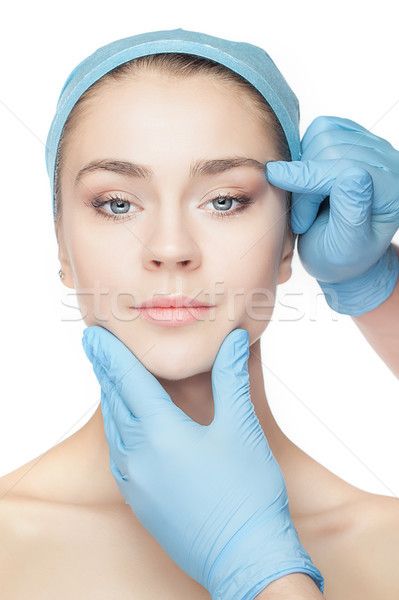 Plastic surgery concept. Doctor hands in gloves touching woman face Stock photo © master1305