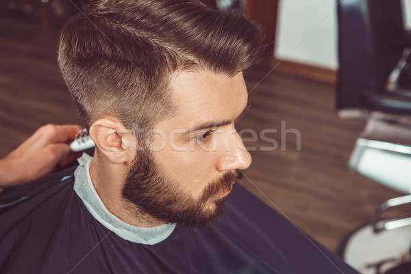 The hands of young barber making haircut to attractive man in barbershop Stock photo © master1305