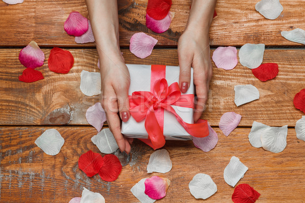 Valentines Day gift and Female hands on wooden background with petals Stock photo © master1305
