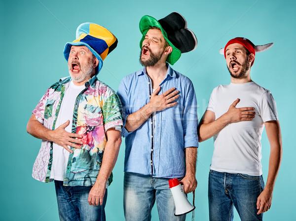 Három futball szurkolók énekel himnusz kék Stock fotó © master1305